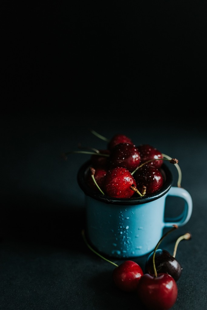 Blue cup filled with fresh cherries on a black background